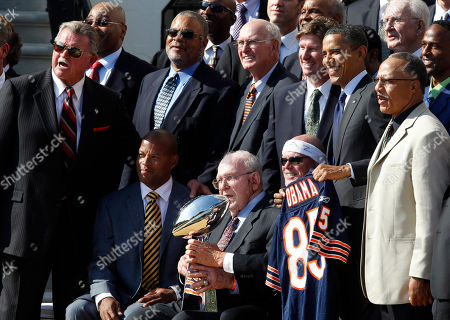Barack Obama, Mike Ditka, Buddy Ryan President Barack Obama stands with the 1985 Super Bowl XX Champions Chicago Bears football team during a ceremony on the South Lawn of the White House in Washington. Pictured are Buddy Ryan, seated with trophy, Mike Ditka, standing left, and Jim McMahon, seated with headband. Buddy Ryan, who coached two defenses that won Super Bowl titles and whose twin sons Rex and Rob have been successful NFL coaches, died . He was 82