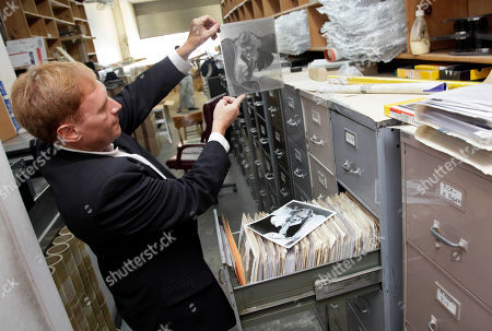 """Stuart Scheinman Stuart Scheinman, a partner in Las Vegas-based Premier Collectibles., looks at an original negative of actress Bette Davis in the files of Movie Star News in New York. Movie Star News, a New York institution since 1939 credited with creating the concept of pin-up art, has been shuttered, and with it nearly 3-million Hollywood-related posters, vintage photographs and original negatives are destined for a different future. Last week, the Manhattan store announced it had sold its entire inventory, including 1,500 original bondage images of the """"Queen of Pin-Ups"""" Bettie Page, to two partners of a Las Vegas collectibles company for an undisclosed sum"""
