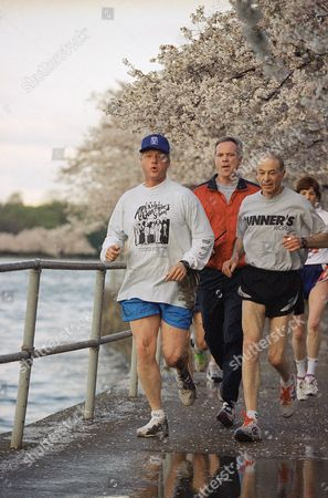 """Bill Clinton With mud covering his leg, shirt and shoes, President Bill Clinton jogs under the cherry blossoms along the Tidal Basin in Washington on . The president took a spill while jogging, White House spokeswoman Dee Dee Myers said it was """"just a minor slip, he dusted himself off, got back on trail"""