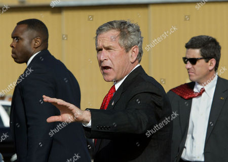 BUSH President Bush gestures to reporters after landing at the Santa Fe Municipal Airport in Santa Fe, N.M., . Bush is spending a private weekend in Santa Fe at the home of friend Roland Betts. Bush is flanked by Secret Service agents