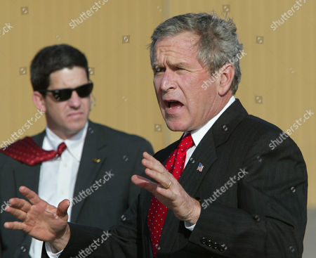 BUSH President Bush gestures to reporters after landing at the Santa Fe Municipal Airport in Santa Fe, N.M., . Bush is spending a private weekend in Santa Fe at the home of friend Roland Betts. A Secret Service agent stands by at left