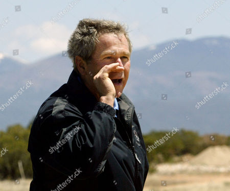 BUSH President Bush shouts to reporters as he prepares to tee off at the Las Campanas course in Santa Fe, N.M., where he is spending a private weekend with friend Roland Betts, . The Sangre de Cristo mountains are seen in the background