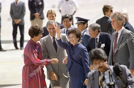 Corazon Aquino,r George Deukmejian, Gloria Deukmejian Philippine President Cory Aquino turns after greeting California Governor George Deukmejian (center) and his wife, Gloria (left) to wave to supporters gathered to welcome her to San Francisco International Airport in San Francisco on . Aquino stopped in San Francisco briefly before continuing to Washington