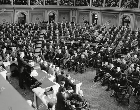 """Franklin Roosevelt, Frank Walker, Francis Biddle, Hennry Stemson, Henry Corgenthau, Wallace White Jr, Walyter Georg, Henry Byrd, James Davis, Robert Reynolds, Rufus Holman Members of his cabinet and congress in joint session heard President Franklin Roosevelt demand in the house chamber, that superiority of the United States be """"overwhelming."""" """"It must be done and we have undertaken to do it."""" He told serious-faced senators and congressmen gathered in the house chamber. First row, right side of picture, left to right are: postmaster general Frank G. Walker; Attorney-general Francis Biddle; secretary of War Henry. Stemson, and secretary of treasury Henry Corgenthau Jr. second row (first complete row), (left to right): senators Wallace H. White Jr. (R-Me); Walter F. George (D-Ga); Harry F. Byrd (D-Va); James J. Davis (R-Pa); Robert Reynolds (D-Nc); Rufus C. Holman (R-Ore); Kenneth McKellar (D-Tenn); Charles L. McNary (R-Ore); third row, left to right are: Senators John Thomas (R-Ida); George D. Aiken (R-VT); Elmer Thomas (D-OKLA) Elbert D. Thomas (D-Utah); James H. Hughes (D-Del); Edwin C. John. (D-Cold). Left to right are: Senators Dennis Chavez (D-Nm); Joseph H. Ball (R-Minn); Ralph O. Brewster (R-Me); Josiah W. Bailey (D-Nc); James M. Mead (D-Ny); Harold H. Burton (R-Ohio). On right end of fifth row, Rep. Joseph Martin (R-Mass), house minority leader. Nearest President's left hand is Rev. James Shera Montgomery, house chaplain"""