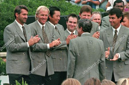 THOMSON Presidents Cup International Team members, from left, Frank Nobilo, Greg Norman, Jumbo Osaki, Craig Perry and Ian Baker-Finch applaud their team captain, Peter Thomson, back to camera, during opening ceremonies for the event in front of the Robert Trent Jones Clubhouse in Gainesville, Va