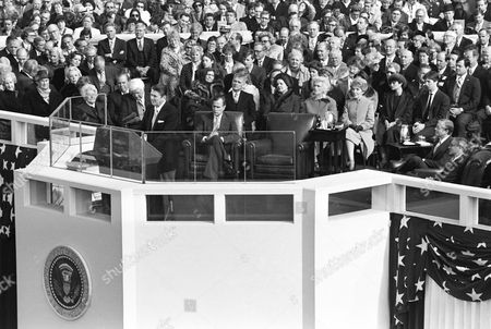 U.S. President Ronald Reagan delivers his inaugural address after being sworn in at the Capitol in Washington, D.C., . From right are: outgoing Vice President Walter Mondale; outgoing President Jimmy Carter; Reagan's son Ronald and his wife, Doria; Reagan's wife Nancy; Barbara Bush, wife of Vice President George Bush. Bush sits at center with his legs crossed. Sen. Mark Hatfield, R-Or., is behind Bush. Visible over the microphones are House Speaker Thomas P. O'Neill, D-Mass., first row,and Rep. John Rhodes, R-Ariz., second row