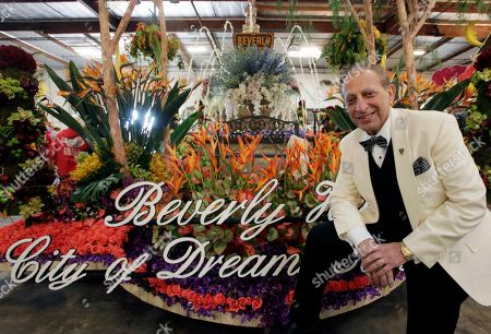 Stock Image of Beverly Hills Mayor Jimmy Delshad poses for a photo in front of the Beverly Hills rose float prior to moving it to Pasadena in preparation for the Rose Parade at a warehouse in Irwindale, Calif. on