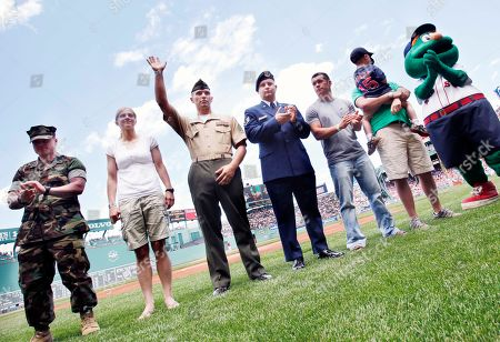 Current and former members of the U.S. military, from left, Robert Tuck, of Manchester, N.H., Katie Kimes, of Loudon, N.H., Christopher Girouard, of Nashua, N.H., Brendan Townsend, of Manchester, Derek Ball, of Londonderry, N.H., and John Nadeau, of Loudon, and his son Ethan, 3, are honored before a baseball game between the Kansas City Royals and the Boston Red Sox, in Boston