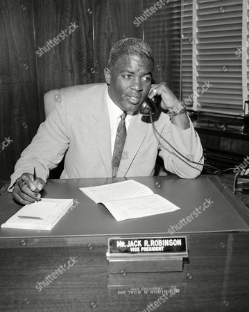 "Robinson Retired baseball legend Jackie Robinson speaks on the phone at his desk in the offices of the Chock Full O' Nuts Company in New York, where he will assume new duties as Vice President in charge of personnel. Robinson is the subject of a two-part documentary, ""Jackie Robinson"" directed by Ken Burns, Sarah Burns and David McMahon airing Monday and Tuesday at 9 p.m. on most PBS stations"