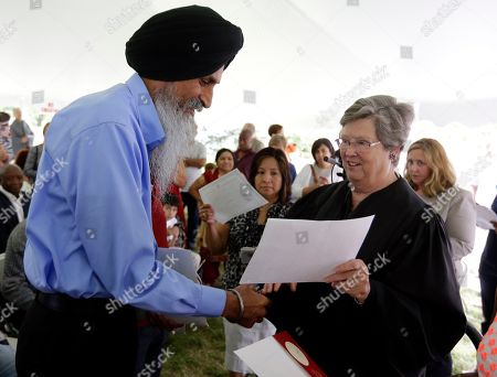 Sukhpal Singh Kalsi, left, receives his Certificate of Citizenship from Judge Sarah Evans Barker at a naturalization ceremony at the Benjamin Harrison Presidential Site in Indianapolis, . Kalsi was one of 101 new citizens at the ceremony. The ceremony was part of an annual celebration of Independence Day by U.S. Citizenship and Immigration Services