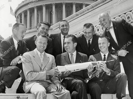 Stock Image of Alan Shepard, Malcolm Scott Carpenter; Waller Schirra Jr; Virgil Grissom; Donald Slayton, and John Glenn Vice President Richard Nixon poses on Capitol steps in Washington, with seven astronauts who are undergoing training for space flight. From left, front row: Leroy Gordon Cooper, Nixon; and Alan Bartlett Shepard; rear row: Malcolm Scott Carpenter; Waller Marty Schirra Jr; Virgil Ivan Grissom; Donald Kent Slayton, and John Herschel Glenn, standing. They are posing with a model of a rocket