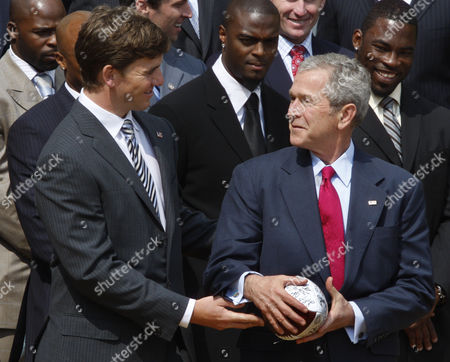 George W. Bush, Greg Gadson, Eli Manning President Bush takes a handoff from Super Bowl XLII most valuable player, New York Giants quarterback Eli Manning as they participate in a photo opportunity on the South lawn of the White House in Washington, honoring the Super Bowl champion New York Giants football team