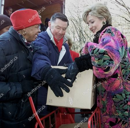 Stock Image of CLINTON JONES Senator-elect Hillary Rodham Clinton, D-N.Y., right, helps Larry Jones, center, president of Feed The Children, put a box with food into a women's cart, in New York's Harlem neighborhood. Clinton lent a hand to Feed the Children as they distributed food to residents of the neighborhood for the holidays