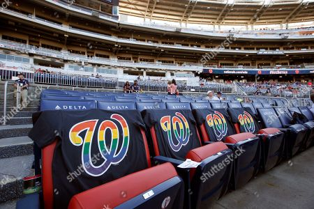 """Billy Bean Rainbow themed t-shirts cover seats before a baseball game between the Washington Nationals and the Chicago Cubs at Nationals Park, in Washington. The Washington Nationals hosted their 12th annual """"Night OUT"""" event, in celebration of the LGBT community"""