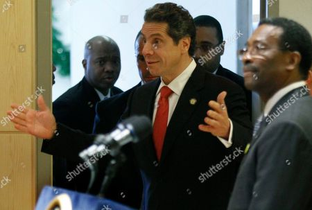 """Gov. Andrew Cuomo, center, reacts to applause as as he arrives to join Medgar Evers College President Dr. William Pollard, far right, on stage for a bill signing ceremony at Medgar Evers College on in Brooklyn, N.Y. Cuomo signed a bill creating """"NY Youth Works,"""" an inner city youth employment program to combat high unemployment in the state's metro areas"""