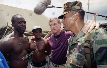 Dan Quayle, Humberto Rodriguez Unidentified victims of Hurricane Andrew, left, talk with Vice President Dan Quayle, center, and Col. Humberto Rodriguez of the U.S. Marines, right, as Quayle toured the tent city area of Homestead, Florida on