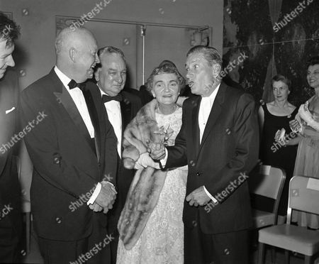 """Songwriter Hoagy Carmichael, right, gets a laugh from President Dwight Eisenhower, left, as he tells a story for Rep. Charles A. Halleck (R-Ind) and Mrs. Halleck before the dinner of the Indiana State Society honoring Halleck as """"Hoosier of the Year."""" The President, who made a short speech at the dinner in Washington on paid tribute to Halleck, Republican leader of the House, as a """"topflight, fighting, tough little Hoosier"""