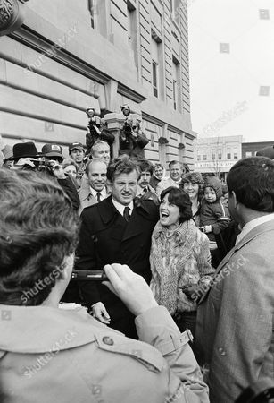 Sen. Edward M. Kennedy (center) is shown on at Newton, Iowa as he asked an enthusiastic Becky Spees if she wanted her picture snapped with him. An obliging spectator accommodated them (foreground) this was an often repeated scene as Kennedy toured the Jasper Co. Courthouse (background) and took a walk around the town square. Kennedy is on a 3-day swing through Iowa in search of support for his bid in seeking his party's presidential nomination