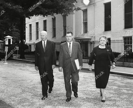 President Dwight D. Eisenhower walks with press secretary James Hagerty and associate press secretary Anne Wheaton with the White House in the background, . They are on the way to the president's news conference in the nearby Executive Offices bldg