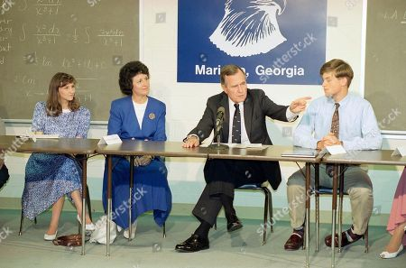 U.S. President George H. Bush takes in a panel discussion of education, at the Mount Paran Christian School in Marietta, Ga. Other panelists are Dr. Mary Stone, school board member, and John Shaw, student, right