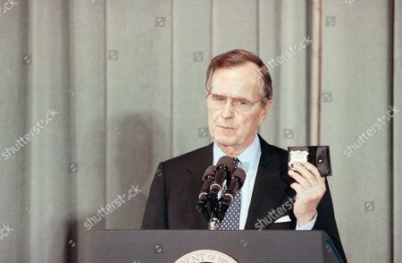 """Stock Picture of U.S. President George H. Bush holds the badge of New York City Patrolman Eddie Byrne, who was killed in 1988 by people who Bush termed """"cocaine cowards,"""" during a speech to Attorney General Dick Thornburgh's anti-crime summit in Washington, . Bush keeps the badge in his Oval Office desk as a reminder of those killed in drug related crimes. Bush said the country should call on the same national will that won the Gulf War to defeat street crime in the nation?s cities"""