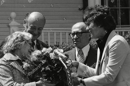 Bess Myerson, hands a Bouquet of roses to Mrs. Aliza Begin, wife of Israeli Prime Minister Menachem Begin, second from right, as New York City Mayor Edward Koch watches, second from left, during a Gracie Mansion ceremony, Thursday, May 4,1978 in New York. Begin is winding up a trip in the U.S. and plans to spend a few days in New York. He arrived from Washington where he met with President Carter