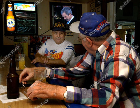 ECHEVERRIA SULLIVAN Joe Echeverria, a 62-year-old Republican, left, trades barbs with Phil Sullivan, a 74-year-old Massachusetts Democrat, as they watch President Bush's inaugural address, at the American Legion Post in Tampa, Fla. Both men are retired veterans of the U.S. Air Force