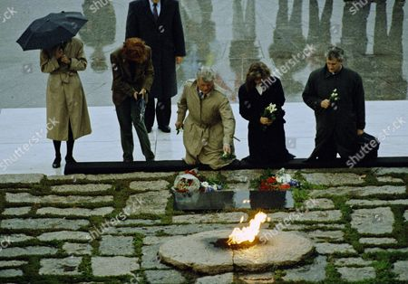 Sen. Edward M. Kennedy, center, places a rose on the grave of his brother, the late John F. Kennedy in Arlington, marking the 28th anniversary of his assassination. He is accompanied by Ed Schlossberg, and his wife Caroline, daughter of the slain President, left, Pat Lawford, far right, and Jean Smith, both sisters