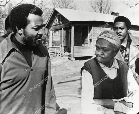 Former football great Jim Brown, left, President of the Black Economic Union, confers with Mrs. Anne Faulkner, 74, in her poor neighborhood at Holly Springs, Miss., . Brown led about 25 black athletes for the firsthand look at conditions his BEU hopes to improve. In background is Leroy Kelly of the Cleveland Browns