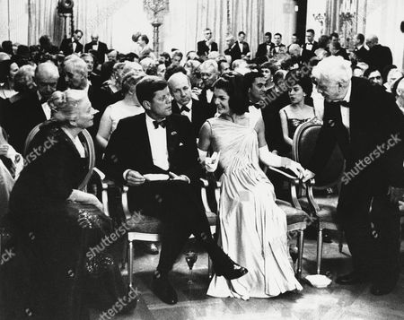 President John F. Kennedy, sitting with wife Jacqueline, look on as poet Robert Frost right and Mrs. Richard J. Walsh (Pearl Buck) exchange greetings in the East Room of the White House on in Washington. The first family and their guests are gathered in the East Room to hear a dramatic reading by actor Fredric March after a dinner honoring winners of the Nobel Prize