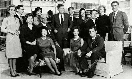 Stock Image of John F. Kennedy, Jacqueline Kennedy Then President-elect John F. Kennedy is surrounded by members of his family in home of his parents in Hyannis Port, Mass., in December, 1960. Standing, left to right Mrs. Robert Kennedy; Steven Smith and wife, Jean Kennedy; Robert Kennedy; sister, Patricia Lawford; Sargent Shriver, brother Ted?s wife, Joan; and Peter Lawford. Foreground, left to right: Eunice Shriver, a sister; Joseph Kennedy, his father, with Mrs. Kennedy seated in front; Mrs. John F. Kennedy; and brother Ted Kennedy