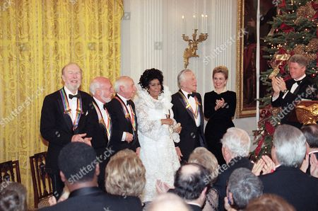 President Bill Clinton and Mrs.Hillary Rodham Clintonapplaud the 1994 Kennedy Center Honors award recipients during a reception in the East Room of the White House. From left to right are songwriter Pete Seeger, director Harold Prince, composer Morton Gould, singer Aretha Franklin, actor Kirk Douglas and the Clintons