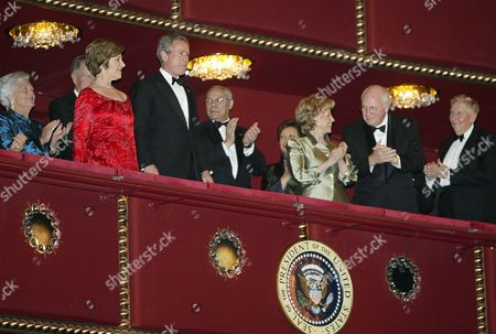 Stock Picture of BUSH CHENEY POWELL President George Bush, third left and first lady Laura Bush, second left, are applaused by Vice President Dick Cheney, second right, Lynne Cheney, third right, former first lady Barbara Bush, left, former president George Bush, (partly obscured) back second left, and Secretary of State Colin Powell, center, as they arrive at a gala performance at the Kennedy Center for the Performing Arts, in honor of James Brown, Loretta Lynn, Carol Burnett, Mike Nichols and Itzhak Perlman, recipients of the 2003 Kennedy Center Honors, in Washington