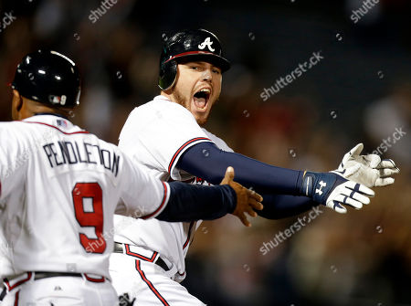 Freddie Freeman, Terry Pendleton Atlanta Braves' Freddie Freeman, right, celebrates while running past first base coach Terry Pendleton after hitting a home run in the ninth inning to beat the Miami Marlins 4-3 to clinch at least an NL wild-card berth for the Braves, in Atlanta