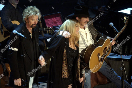 DUNN CASH BROOKS Ronnie Dunn, left, and Kix Brooks perform along with Carlene Carter, daughter of June Carter Cash during the Johnny Cash Memorial Tribute at the Ryman Auditorium in Nashville, Tenn. Cash died on Sept. 12, 2003 at the age of 71, from complications of diabetes. The coat that Dunn is wearing was given to him by Johnny Cash early in his career