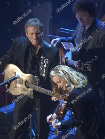 GATLIN CASH SCRUGGS Laura Cash, Johnny Cash's daughter-in-law plays the fiddle while Larry Gatlin and Randy Scruggs look on during the Johnny Cash Memorial Tribute at the Ryman Auditorium in Nashville, Tenn. Cash died on Sept. 12, 2003 at the age of 71, from complications of diabetes