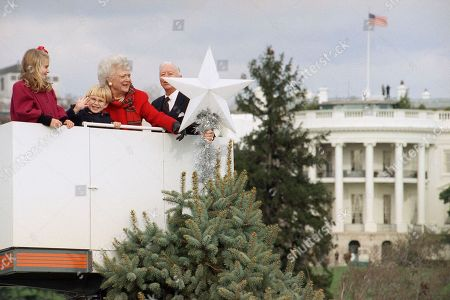 First Lady Barbara Bush, with assistance from her grandchildren Lauren, left, and Pierce Bush, place the main ornament on the top of the National Christmas Tree on in Washington. At right is Joseph Riley, President of the Christmas pageant of Peace Committee