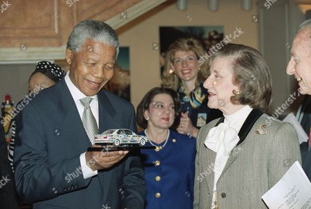 South African President Nelson Mandela holds a model of a painted BMW auto mobile presented to him by National Museum of Women in the Arts chairwoman Wilhelmina Holladay on at the museum in Washington. The South African president toured an exhibit by South African artist Esther Mahlangu at the museum which includes the original mural-painted automobile