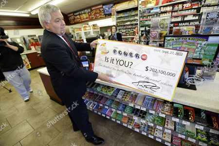 Stock Image of Casey's General Stores Vice President of Marketing Mike Richardson places a Powerball promotional check on the counter in the Casey's store, in Bondurant, Iowa. Iowa Lottery officials say someone bought a winning $202 million Powerball ticket at the store. The ticket matched the six numbers drawn on Wednesday night