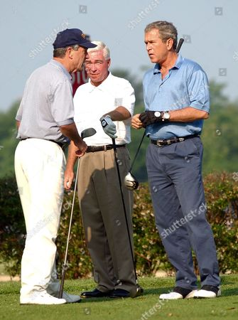 BUSH EVANS THOMAS President Bush chats with Commerce Secretary Don Evans, left, and Mike Thomas, clubhouse manager, before teeing off at the first hole during a golf game at Andrews Air Force Base, Md., . The president was playing with Evans and Thomas as well as Roland Betts, a personal friend