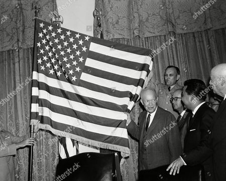 President Dwight Eisenhower helps unfurl the new 50-star flag on in Washington after signing a proclamation making Hawaii the 50th state of the union. At right is Daniel K. Inouye, Democratic congressman-elect from Hawaii. Others are: Lt. Col. James S. Cook Jr. of the Office of the Quartermaster General, and Edward Johnston, center, Secretary of the Hawaii, who represented Gov. -elect William F. Quinn