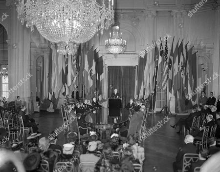 Franklin Delano Roosevelt In this flag-draped setting at the Pan American Union, President Franklin D. Roosevelt is delivering his address at Washington, on the occasion of the union's 50th anniversary. Members of the governing board are seated around oval table. From front of table reading left: Dr. L.S. Rowe, director general; Dr. Jose T. Baron, charge d'affaires of Cuba; Dr. Julian R. Caceres, minister from Honduras (not visible); Dr. Elie Lescot, Haitian minister; Dr. Ricardo Castro Beeche, Costa Rican minister; Don Jose Richling, Uruguayan minister; Dr. Gabriel Turbay, Colombian ambassador; Dr. Diogenes Escalante, Venezuelan ambassador; Capt. Colon E. Loy Alfaro, ambassador from Ecuador; Dr. Felipe A. Espil, ambassador from Argentina; Dr. Hector David Castro, minister from El Salvador; the president; Secretary of State Cordell Hull; Dr. Manuel de Freyrety Santander, Peruvian ambassador; Dr. Francisco Castillo Nejera, Mexican ambassador; Dr. Carlos Martins, Brazilian ambassador; Dr. Alberto Cabero, Chilean ambassador; Dr. Jorge E. Boyd, Panamanian ambassador; Dr. Andres Pastoriza, minister from Dominican Republic; Pastoriza, minister from Dominican Republic; Dr. Leon de Bayle, Nicaraguan minister; Dr. Horacio A. Fernandez, Paraguayan minister; Dr. Enrique Lopez Herrarte, charge d'affaires of Guatemala