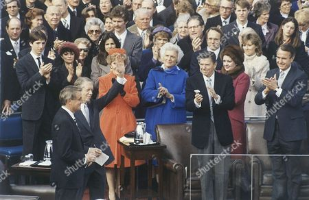 Jimmy Carter, George H.W. Bush, Ronald Reagan, Barbara Bush, Nancy Reagan Walter Mondale, Patti Davis, Maureen Reagan Outgoing President Jimmy Carter, second from right, waves farewell at the Capitol in Washington Jan,20, 1981 after President Ronald Reagan was sworn in as the nation's 40th President. From left are: Vice President George Bush; President Ronald Reagan; Barbara Bush; Nancy Reagan; Jimmy Carter; and outgoing Vice President Walter Mondale. Visible at center is Maureen Reagan and Patti Davis, daughters of President Reagan. At upper right is Ronald P. Reagan and his wife Doris