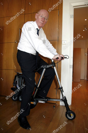 Clive Sinclair on his A Bike at his London office