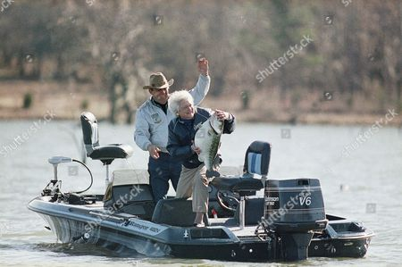 First Lady Barbara Bush, center, holds a mounted large-mouth bass as she and fishing partner Ray Scott attempt to make the President think she caught the fish, Pintlala, Ala. She and President Bush were in Pintlala on New Years Day for a bass fishing trip