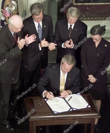 Stock Image of LOTT President Bush, is surrounded, left to right, by Sen. Phil Gramm, R-Tex, Sen. Trent Lott, R-Miss, Sen. Zell Miller, D-Ga, and the late Sen. Coverdell's wife, Nancy Coverdell, as he signs a bill at the Eisenhower Executive Office Building in Washington, naming the Peace Corps Headquarters building in Washington, D.C., and the Peace Corps' World Wise Schools program after the late Senator Paul Coverdell. The bill also appropriates $10 million for the construction of the Paul D.Coverdell Building at the University of Georgia in Athens