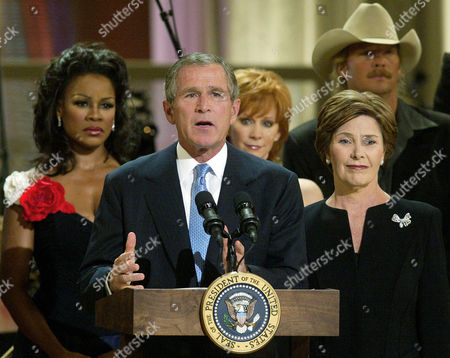 BUSH President Bush and first lady Laura Bush make remarks during a performance at the John F. Kennedy Center, commemorating the Sept. 11. anniversary. The President's Committee on the Arts and the Humanities hold a free two-hour performance in honor of the victims of the Sept. 11 attacks and their families. From left to right, musical artists Denyce Graves, left to right, Reba McEntire, Alan Jackson are seen in the back ground