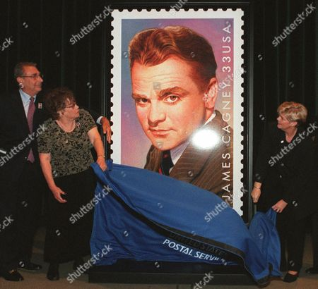 Stock Picture of THOMAS WILLHITE REISENBACH Casey Thomas, daughter of actor James Cagney, left of stamp, pulls a veil from a new commemerative stamp honoring her father during a ceremony at Warner Brothers Studios in Burbank, Calif., . At right is Deborah Willhite, senior vice president, Government Relations, U.S. Postal Service and at left is Sanford Reisenbach, Executive Vice President at Warner Brothers