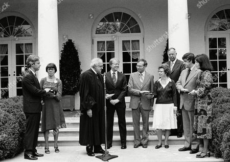 President Jimmy Carter, center, watches as various appointees receive their oath of office from U.S. Circuit Judge David Baselon during a ceremony in the White House Rose Garden, in Washington. From left: Richard C. Atkinson, director of the National Science Foundation; his wife, Rita Atkinson; Judge Baselon; President Carter; Dr. Frank Press, director of the office of Science and Technology; his wife, Billie Press; Rep. Paul Rogers (D-Fla.); Dr. Peter Bourne, director of the office of Drug Abuse Policy; and Mary King, wife of Bourne, and deputy director of ACTION, the volunteer agency