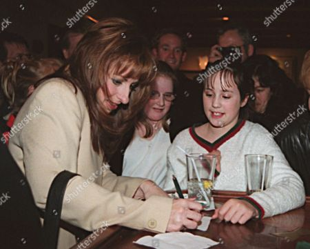 JONES Paula Jones signs her autograph on a napkin for both Ali Miranda, 10, left, and Nicole Zseltvay, 11, both of Maryland, at a restaurant in Washington, where she had dinner with her husband and lawyer. Jones had spent nearly six hours earlier in the day watching President Clinton testify under oath in a sexual harrassment suit brought by her